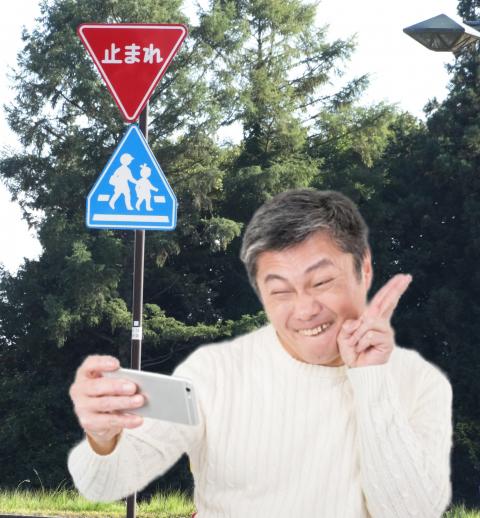 標識と自撮りするおじさん画像